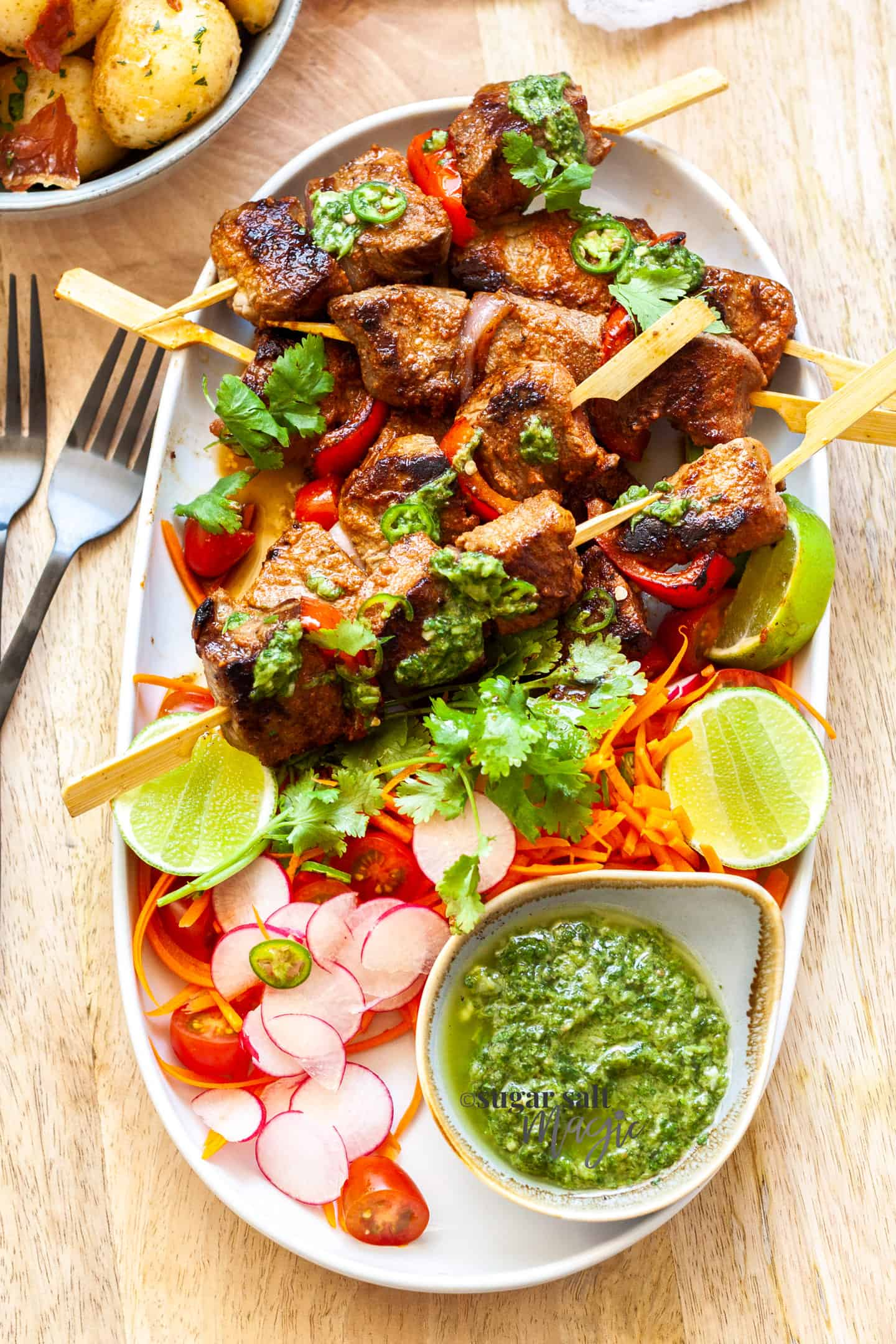 An oval dish filled with salad and steak kabobs with a green sauce.