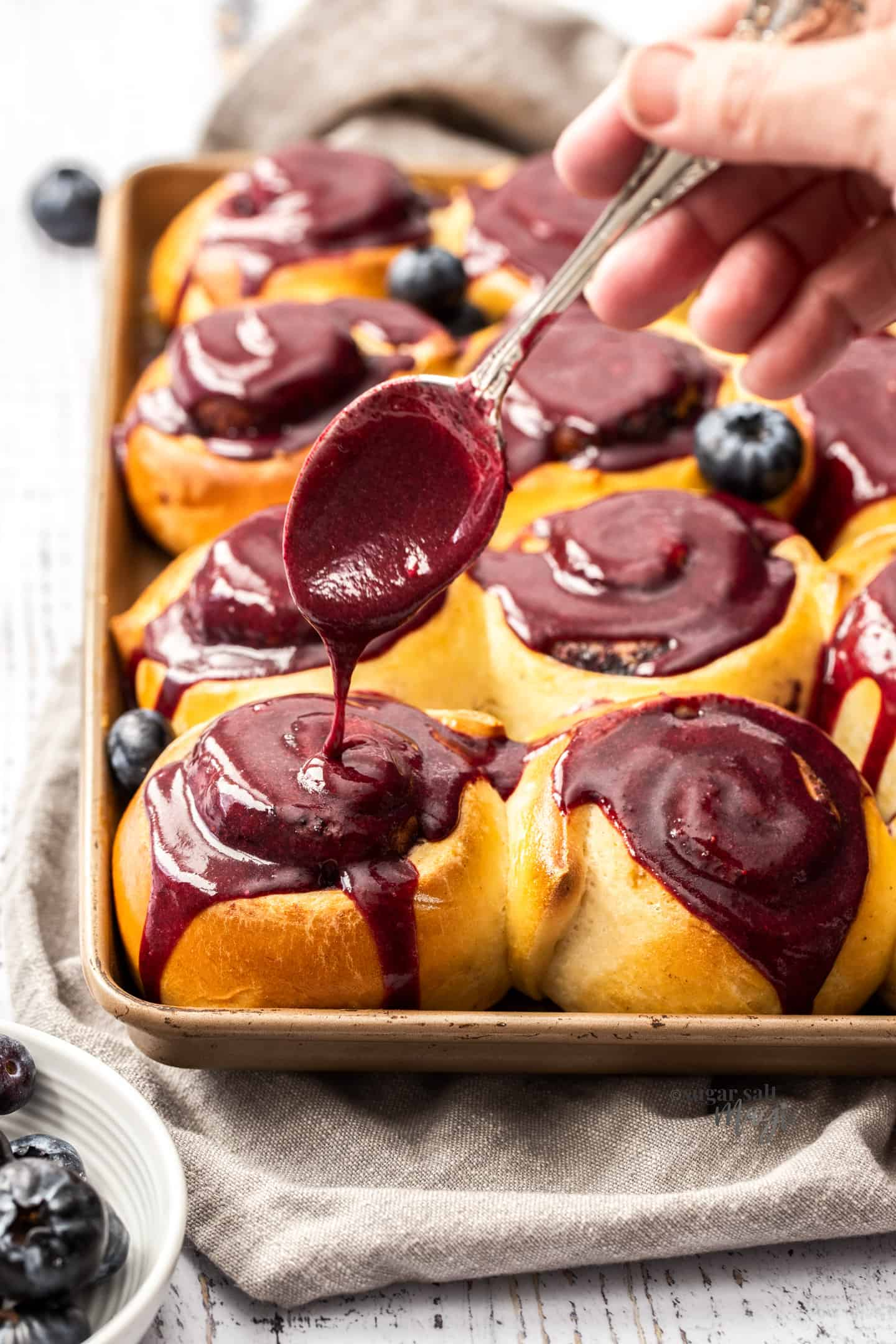 Blueberry glaze being drizzled over the top of cinnamon rolls in a baking tin with a spoon.