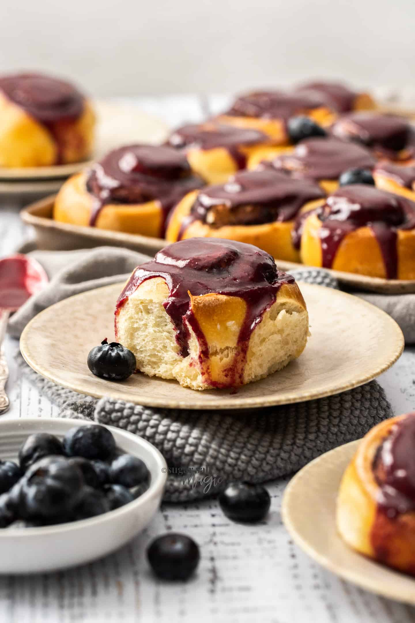 A cinnamon roll topped with blueberry glaze on a cream plate.