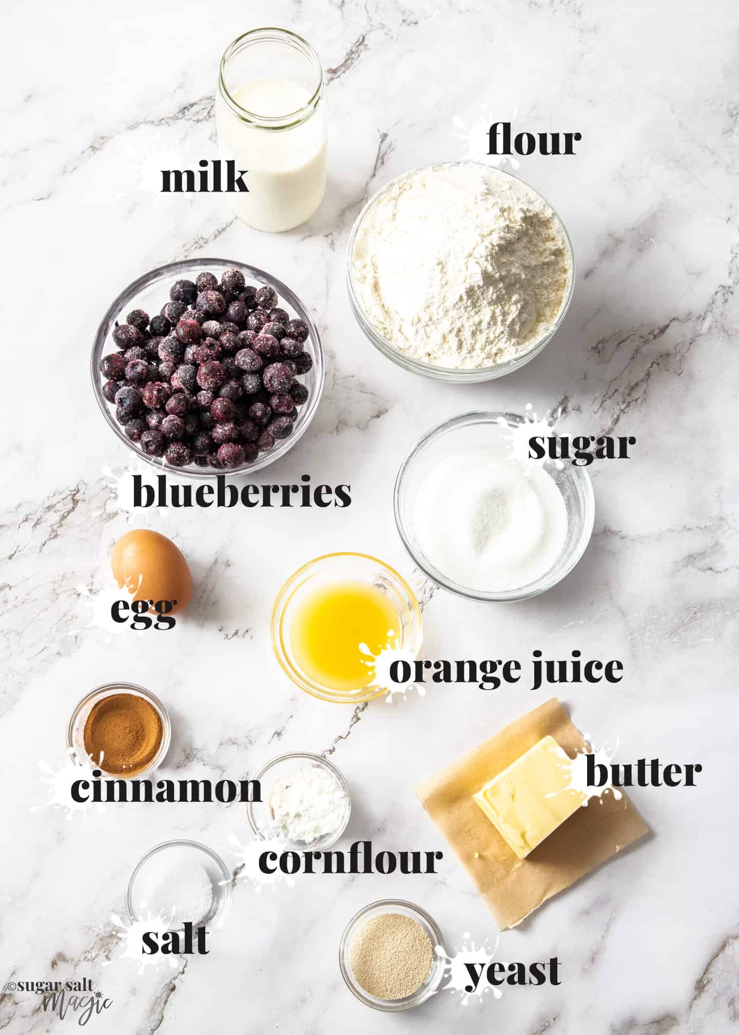 Ingredients for blueberry cinnamon rolls on a marble surface.