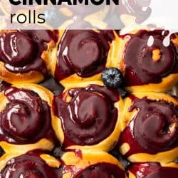 Closeup, top down view of 12 cinnamon rolls covered in blueberry glaze in a baking tin.