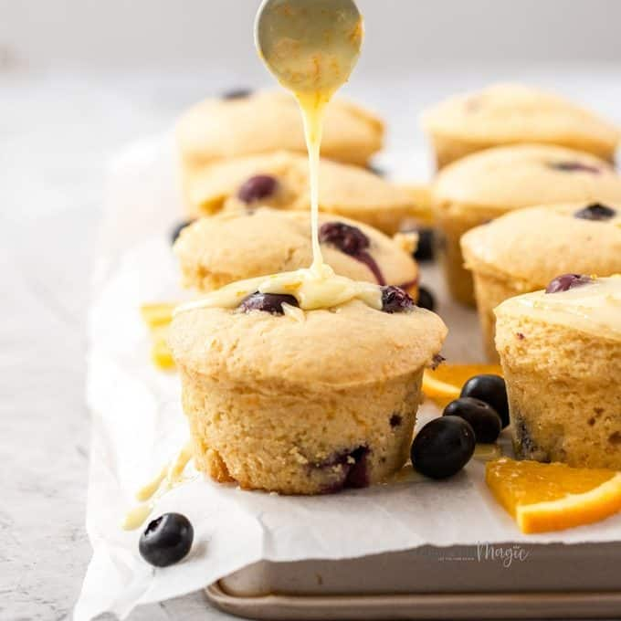 Muffins sitting on a sheet of baking paper on a baking tray. surrounded by blueberries and slices of orange.