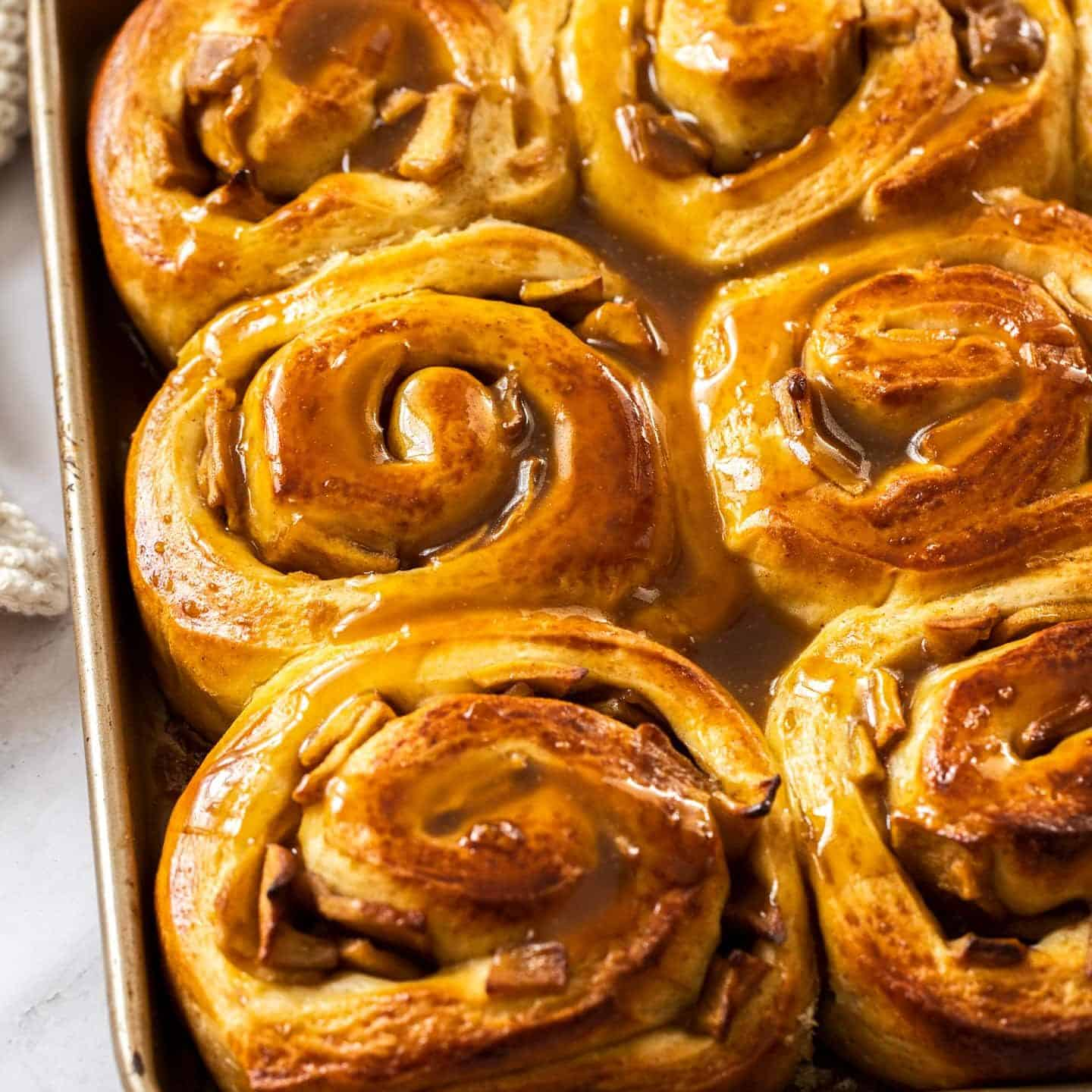 A gold baking tray filled with cinnamon rolls.