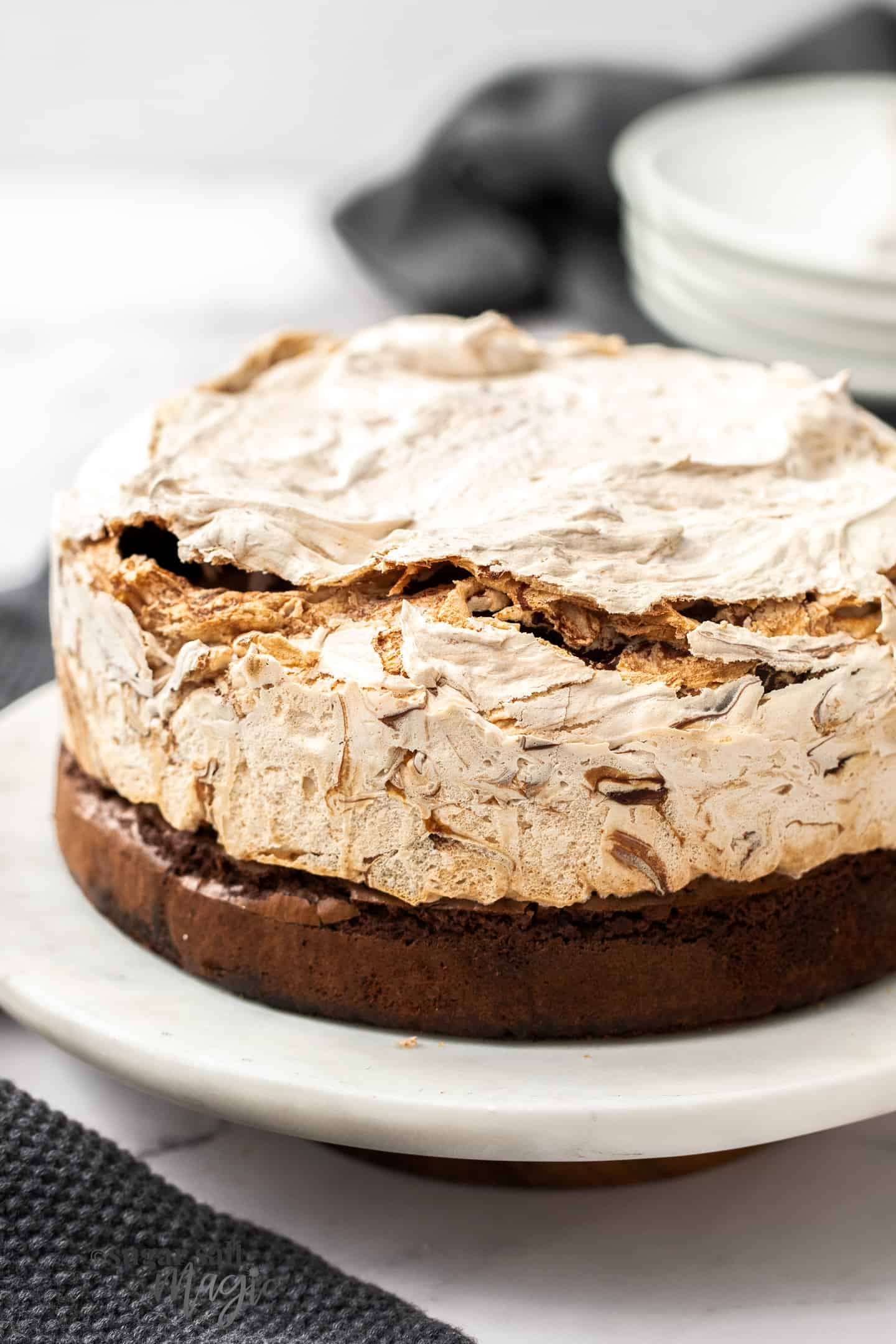 Closeup of a full chocolate meringue cake on a marble platter.