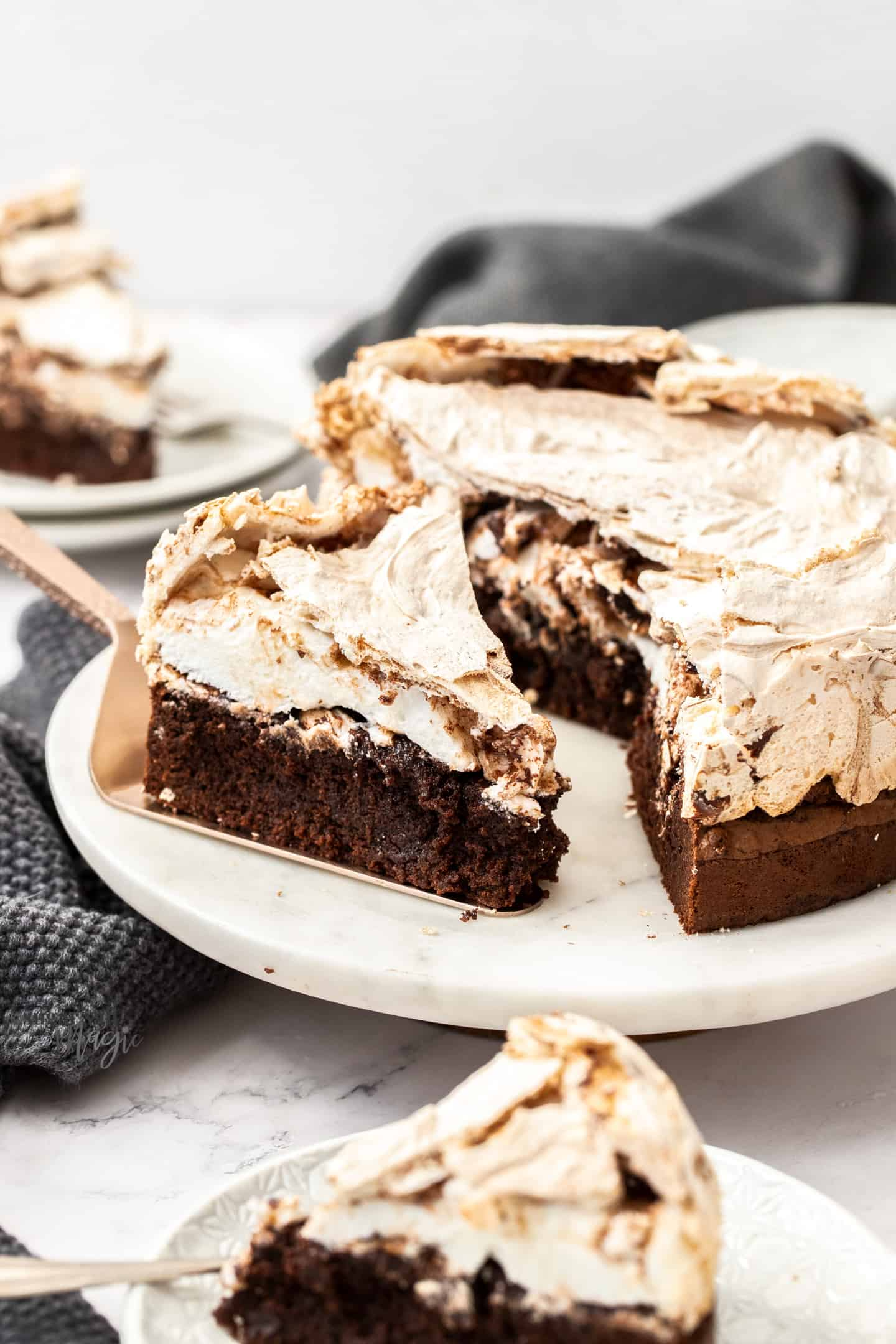 A slice of chocolate meringue cake on a white marble platter.