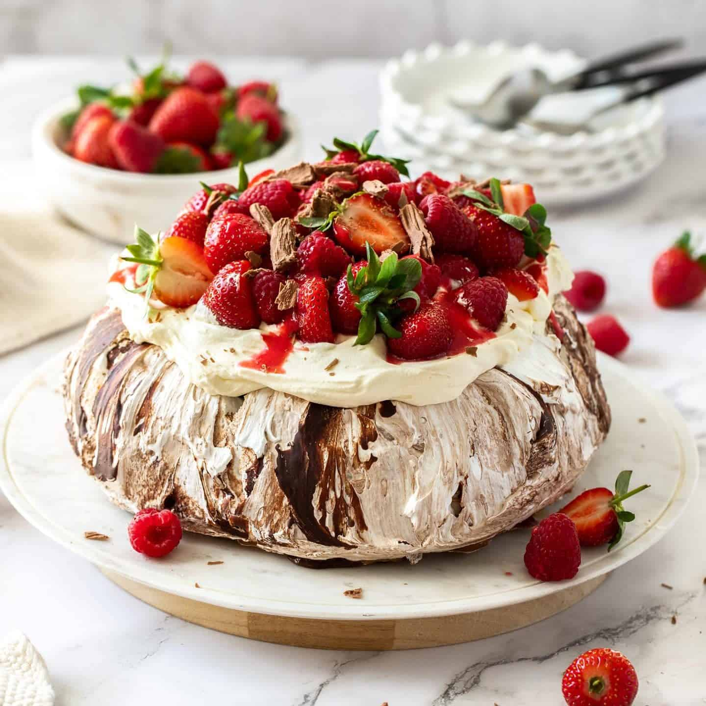 A chocolate pavlova topped with cream and berries on a white cake plate.