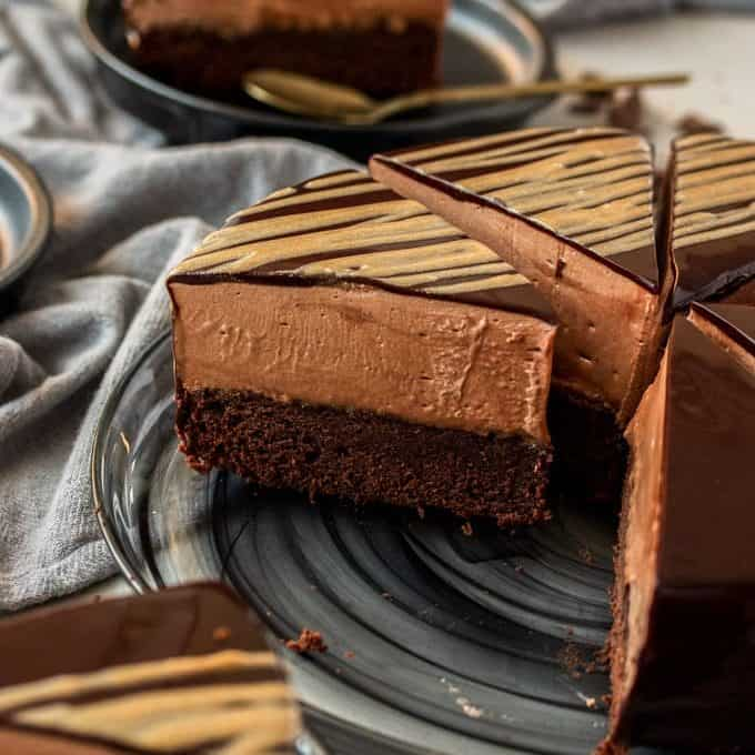 A chocolate mousse mud cake cut into slices on a black glass plate