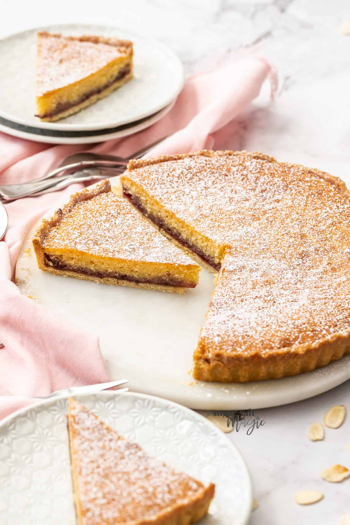 A bakewell tart, with a slice cut out, sitting on a white cake platter.