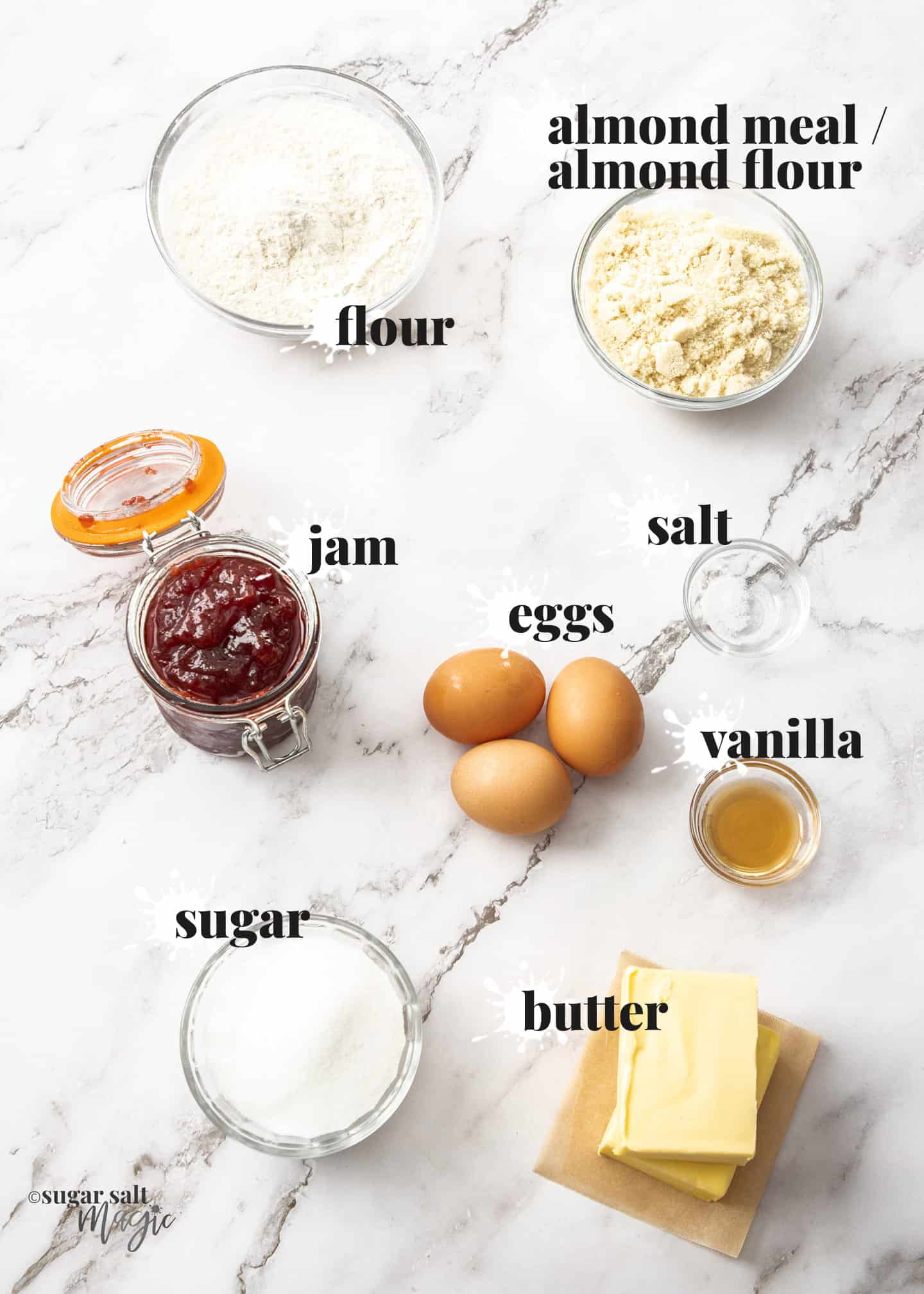 Ingredients for bakewell tart on a white marble surface.
