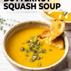 A bowl filled with butternut soup topped with crusty bread and pepitas.