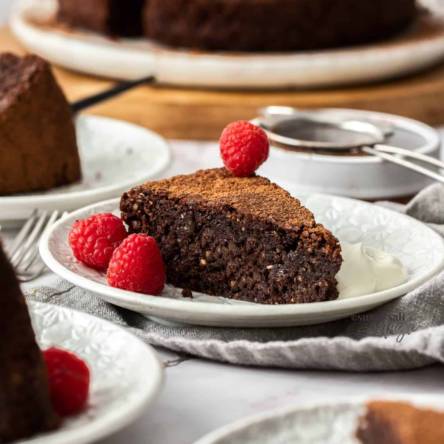 A slice of chocolate cake on a white cake plate with cream and raspberries.