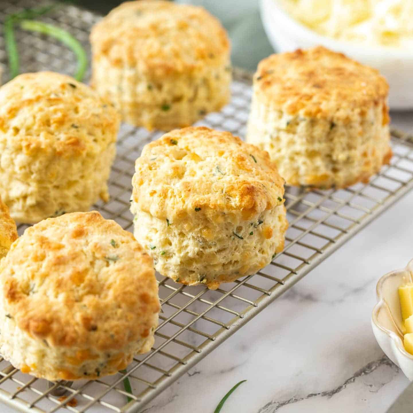 Closeup of 5 cheese scones on a wire cooling rack.