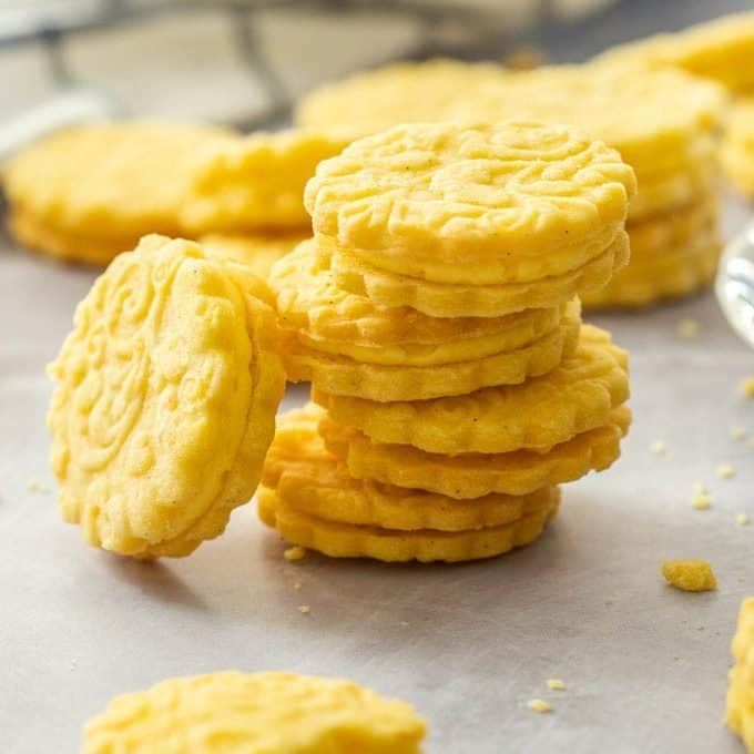 A stack of custard cream biscuits with another leaning up against them. On a grey surface with a striped tea towel at the back.