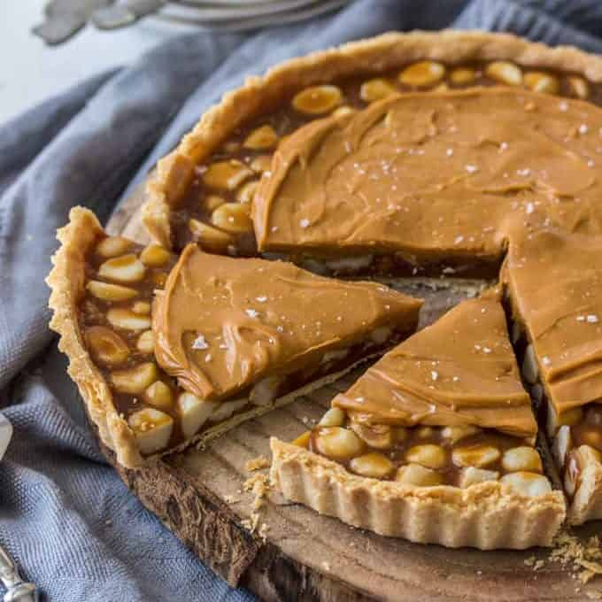 A caramel tart filled with macadamias on a wooden board with a slice cut out.