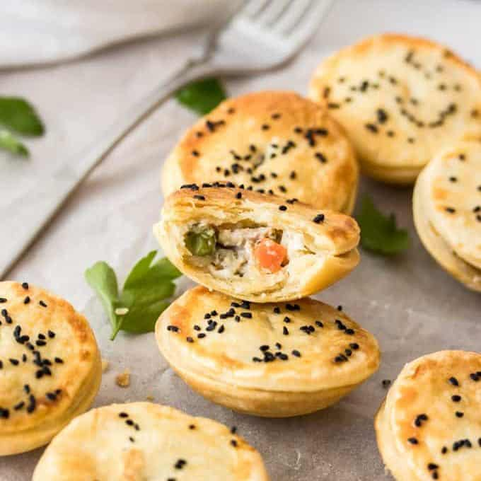 A batch of miniature chicken pot pies with one broken open showing the filling.
