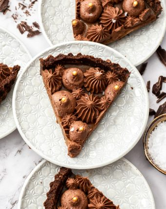 Top down view of 3 slices of chocolate caramel tart on white dessert plates.