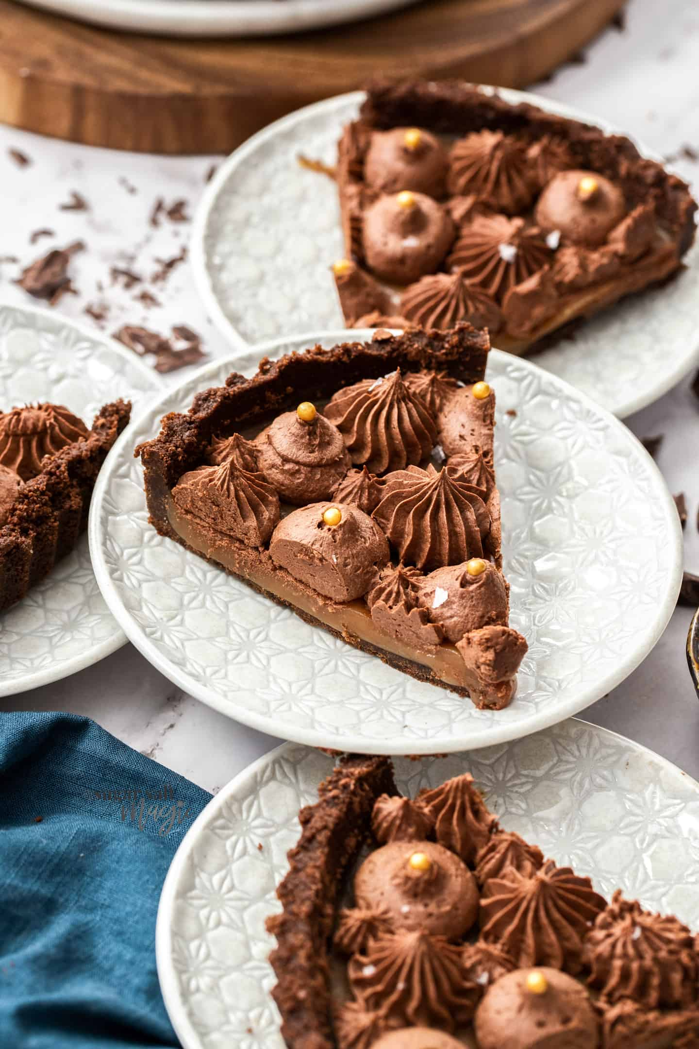 3 slices of chocolate caramel tart on white dessert plates with piped ganache stars on top.