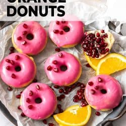 6 donuts with pink frosting, surrounded by orange slices and pomegranate seeds.
