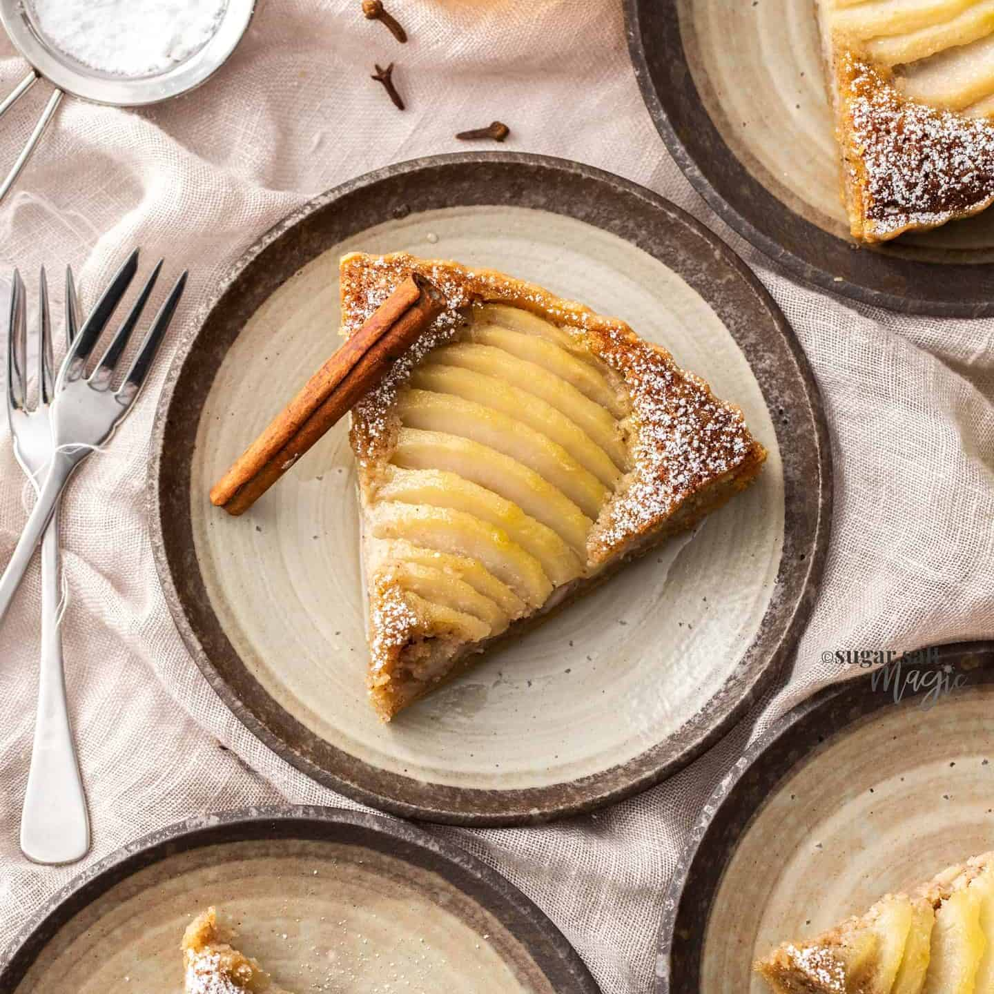 4 small cake plates, each with a slice of pear tart.