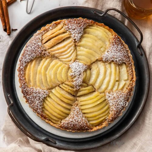 Top down view of a tart with 6 sliced pears in it.