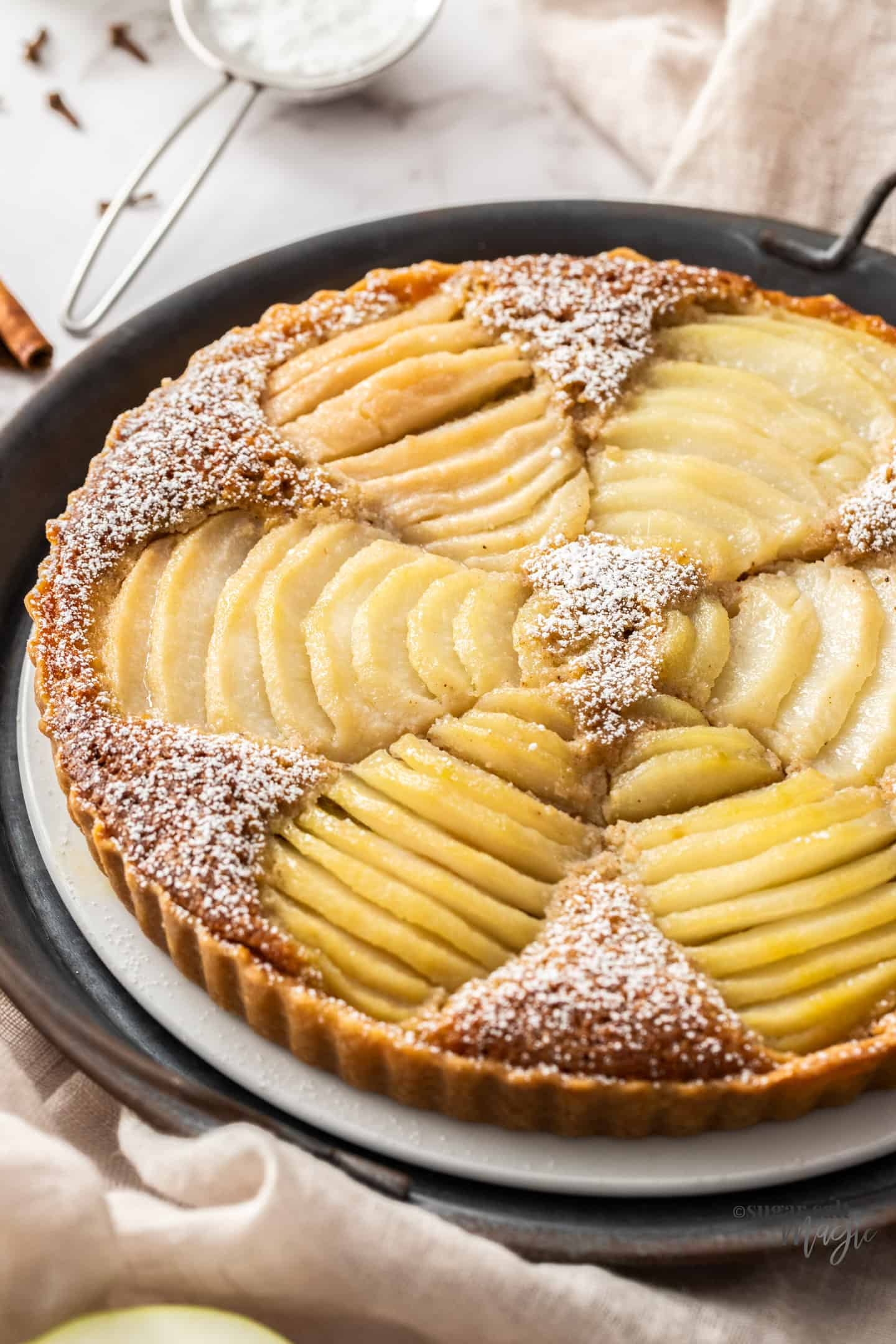 A tart filled with slices of pears on a white cake plate. A small sieve of icing sugar in the background.