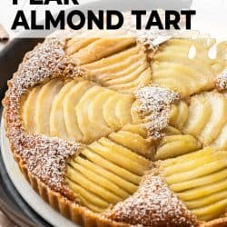 A tart filled with pears on a white cake plate.