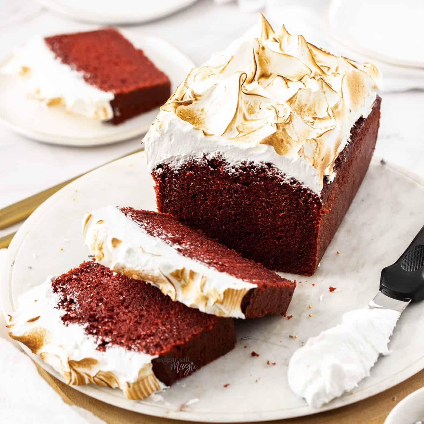 Red velvet cake on a white platter with two slices cut from it.