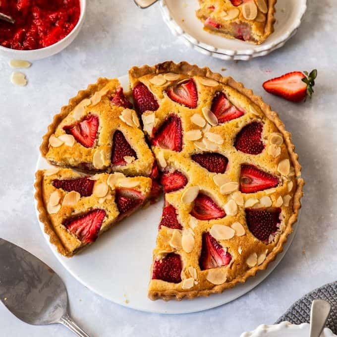 Birdseye view of a strawberry tart on a white plate. A cake slice sits in front and dessert plates are set around it.