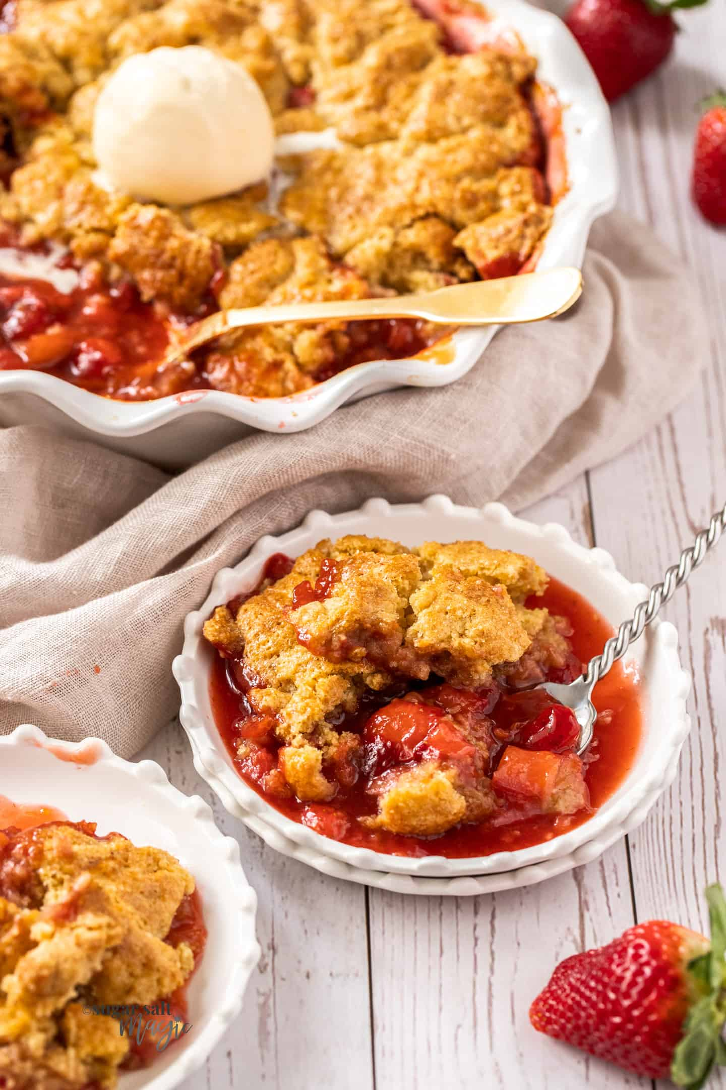 A small white dessert plate filled with strawberry rhubarb cobbler.