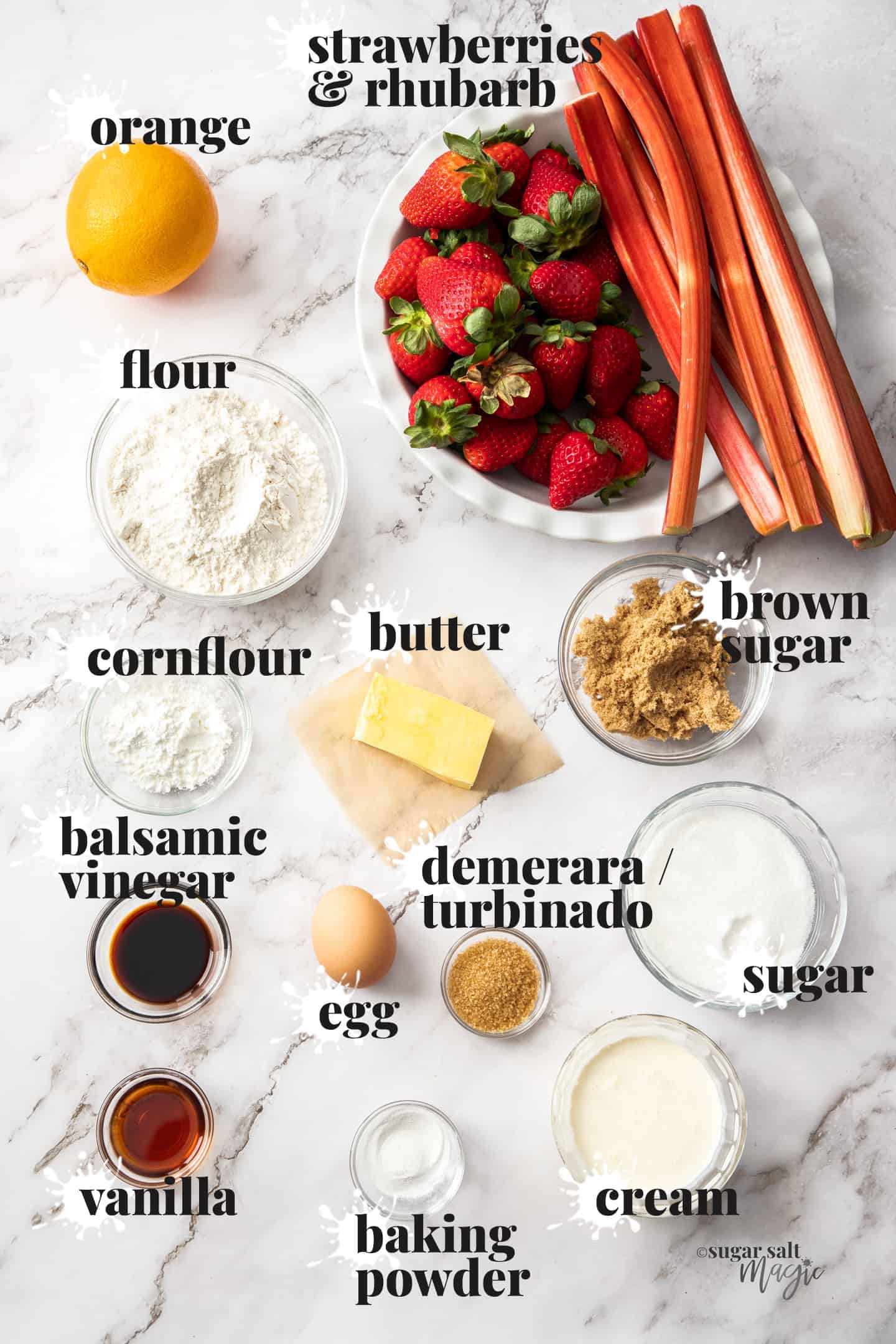 Ingredients for strawberry rhubarb cobbler recipe laid out on a marble benchtop.