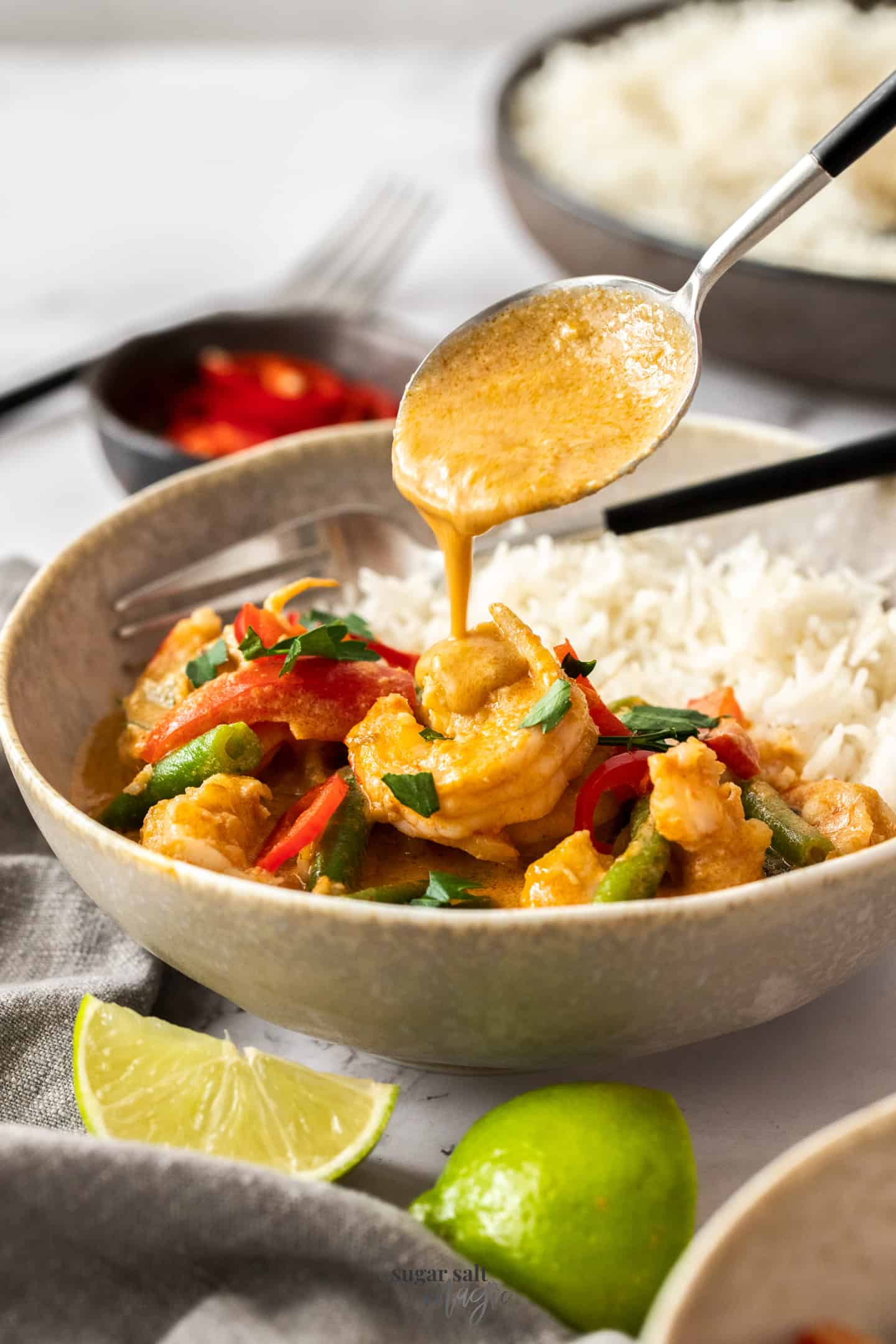 Sauce being poured over prawns in a bowl with rice.