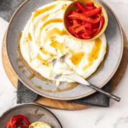 Goats cheese spread over a large grey plate with a small bowl of roasted peppers next to it.