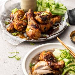 A metal tray filled with chicken drumsticks and cucumber ribbons.