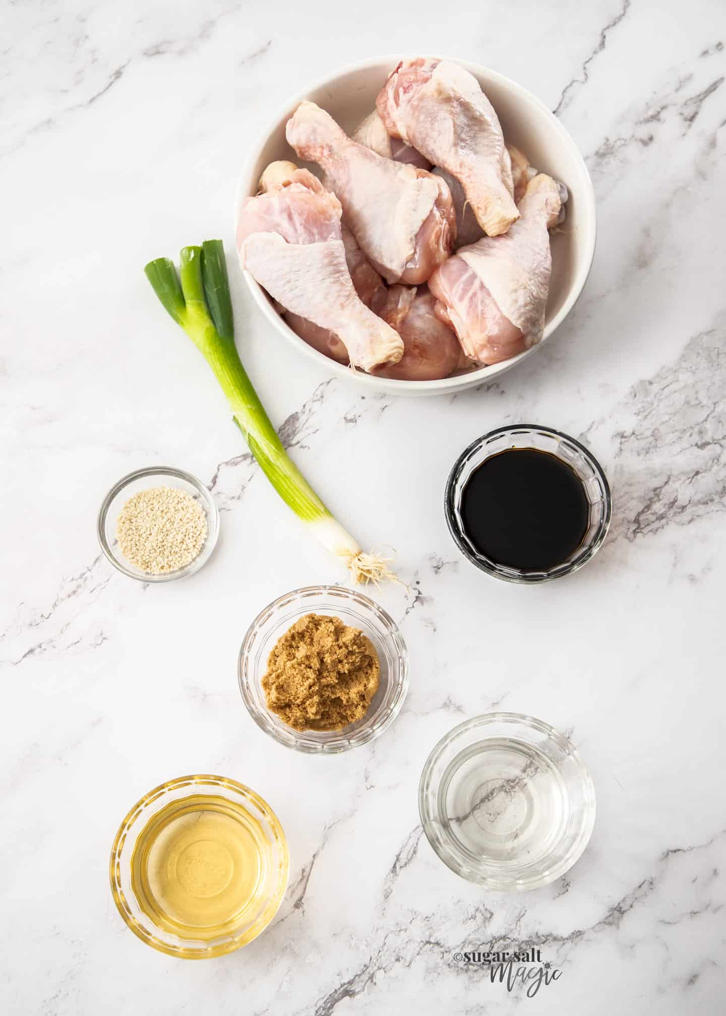 Ingredients for air fryer chicken drumsticks on a marble benchtop.