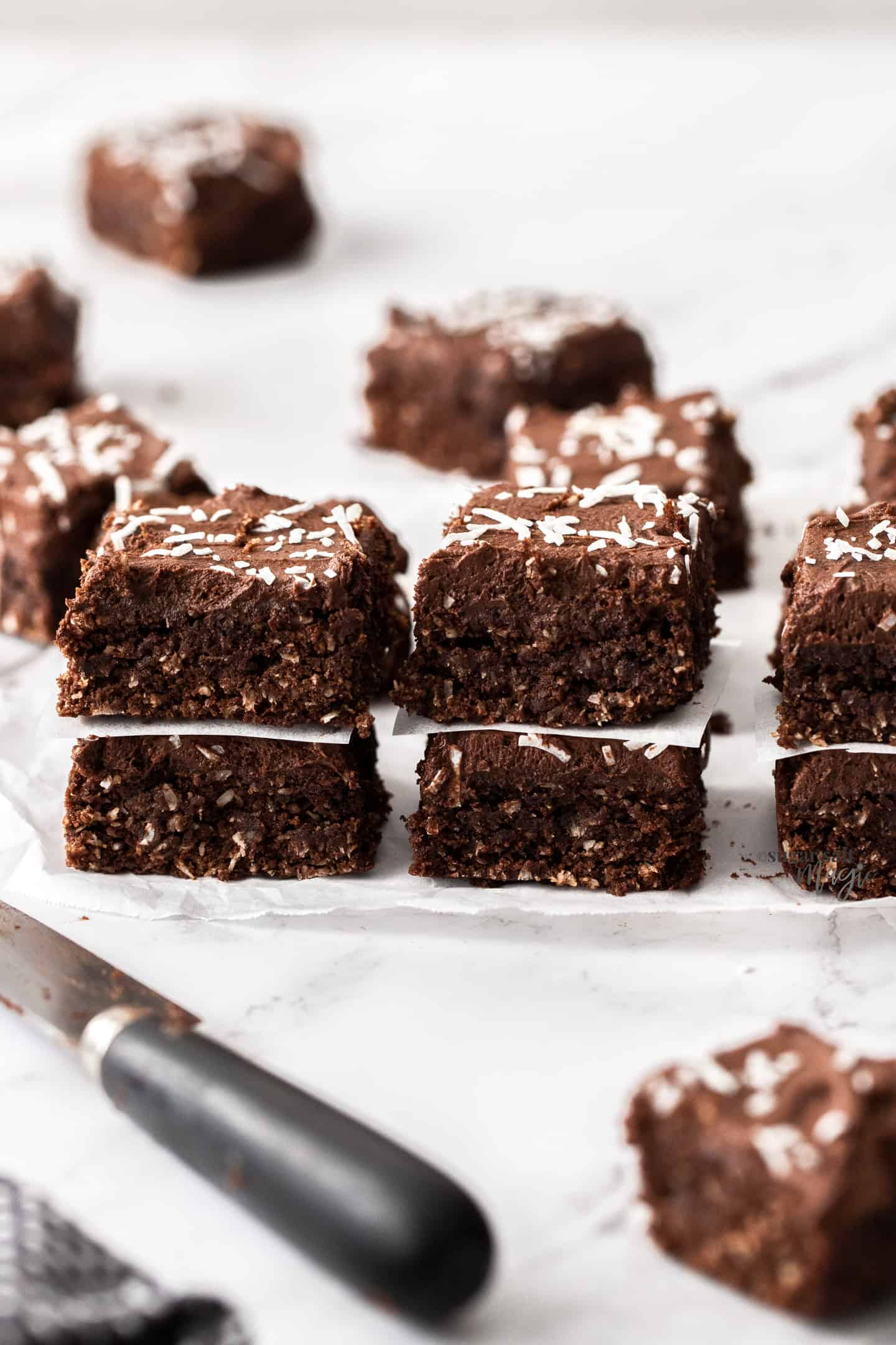 3 stacks of 2 pieces of coconut chocolate fudge slice with a knife in front.