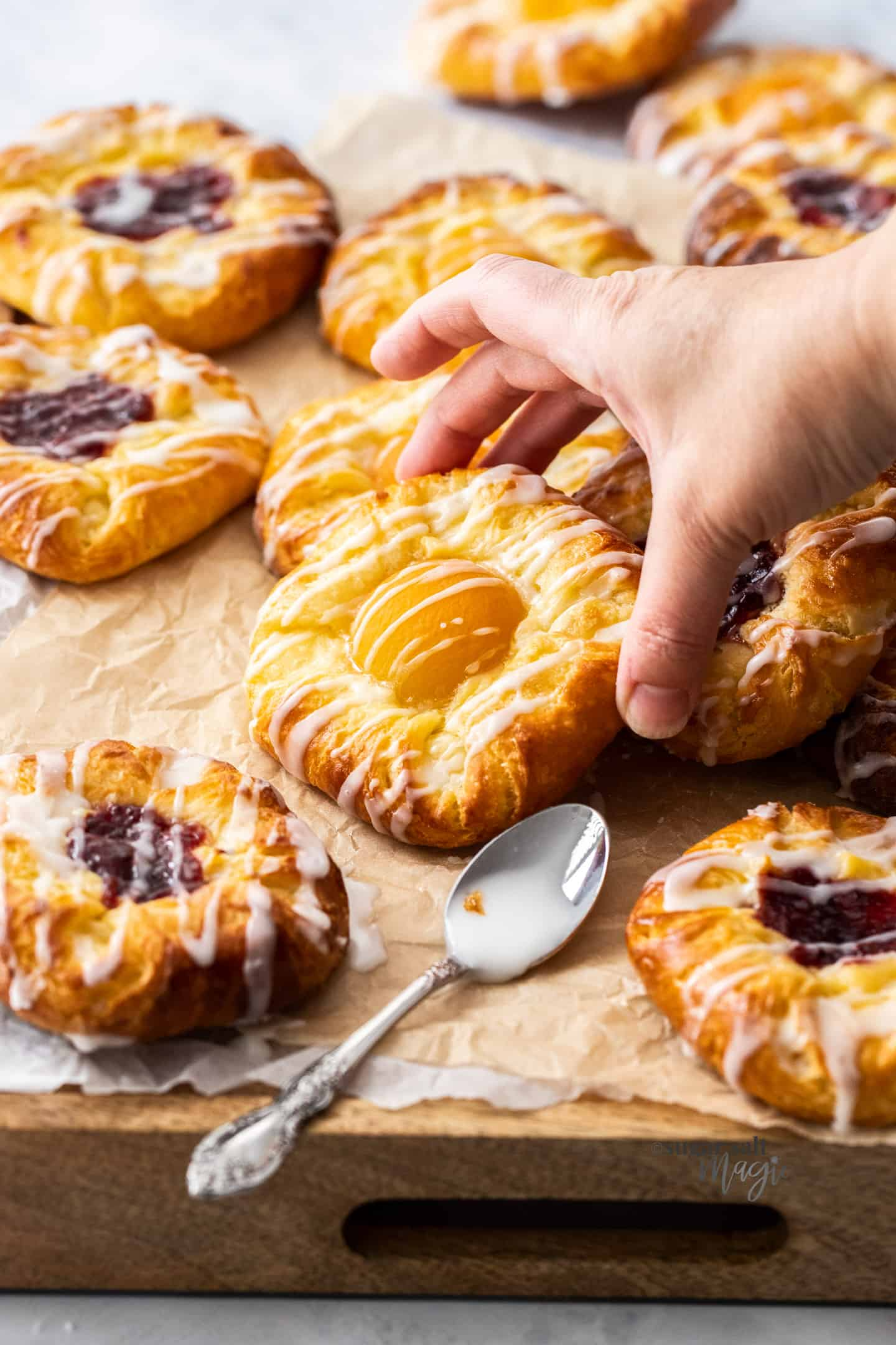 A hand reaching in to pick up an apricot danish from a wooden board.