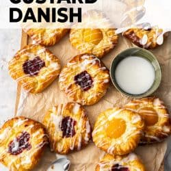 A batch of fruit custard danish pastries on a sheet of baking paper.
