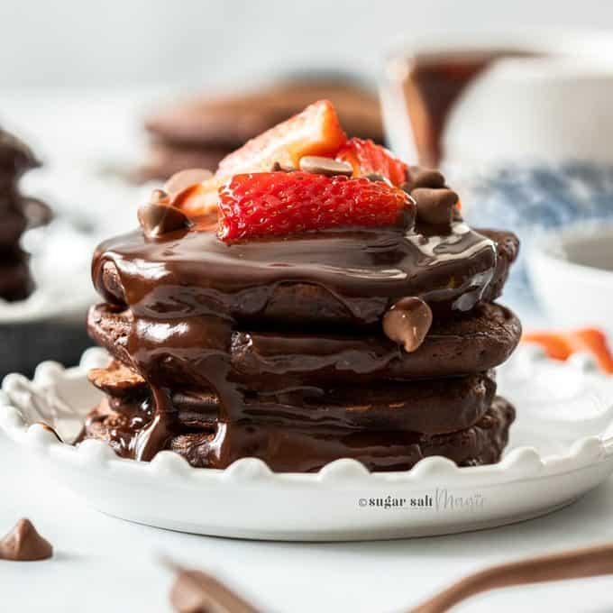 A stack of chocolate pancakes on a white plate, topped with strawberries chocolate chips and chocolate syrup.