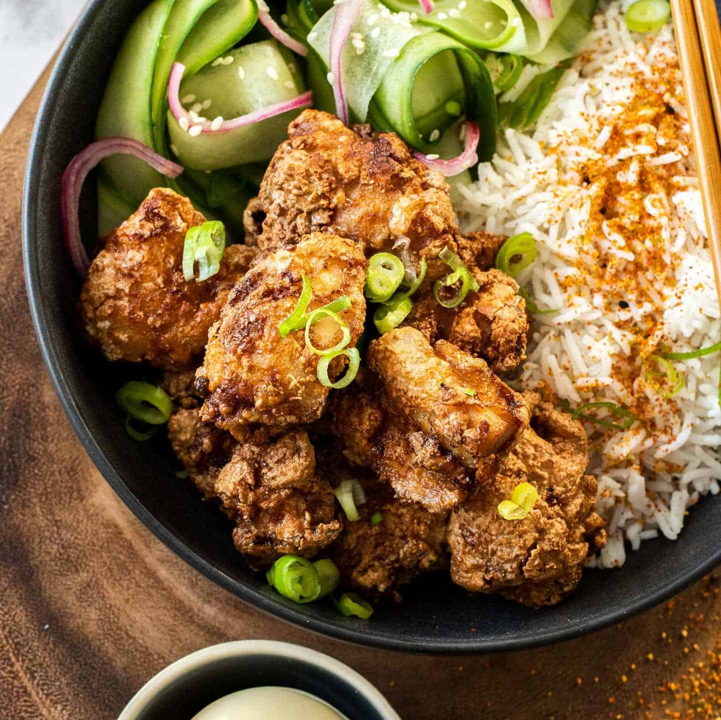 A black bowl filled with rice and fried chicken.