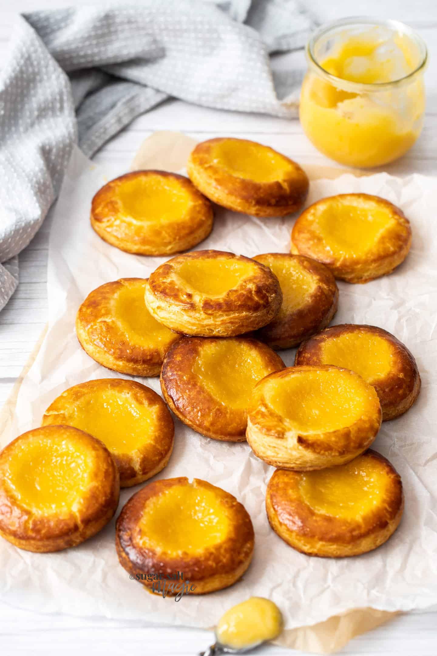 13 lemon danish pastries on a sheet of baking paper.