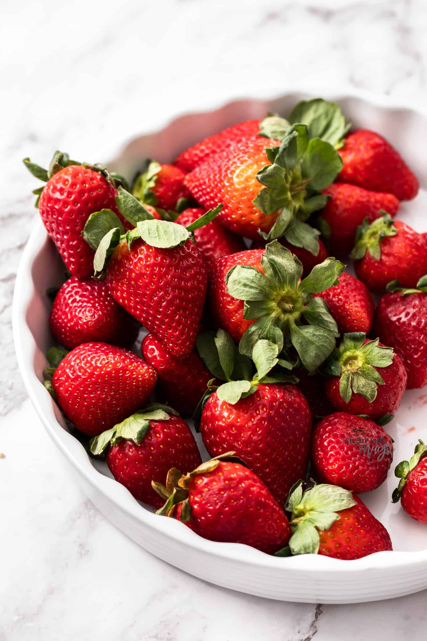 A white pie dish filled with fresh strawberries.