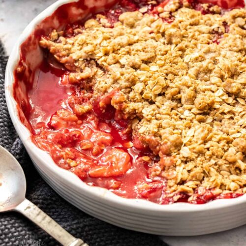A white pie dish filled with baked strawberry crisp.