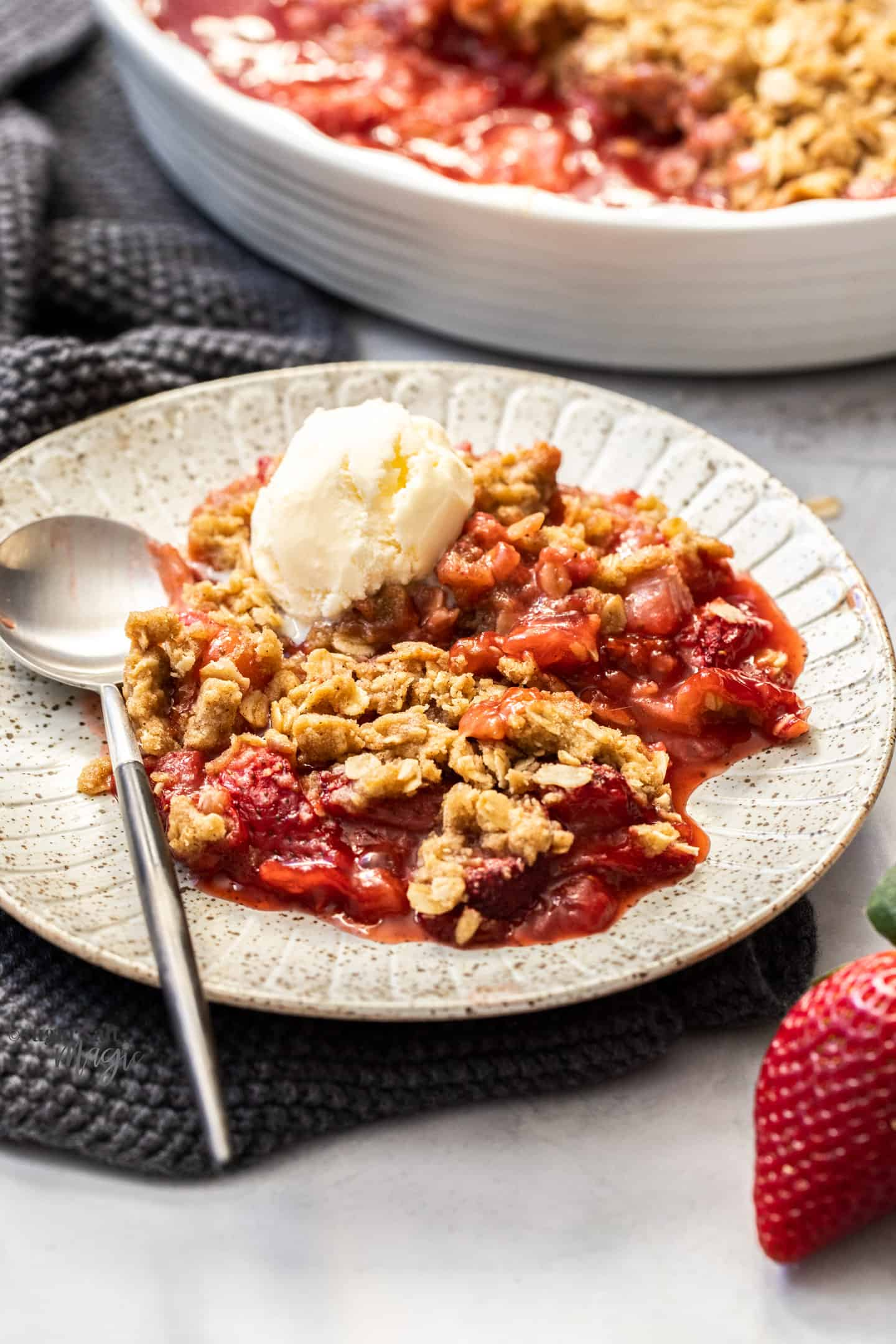 A plate filled with strawberry crisp and ice cream