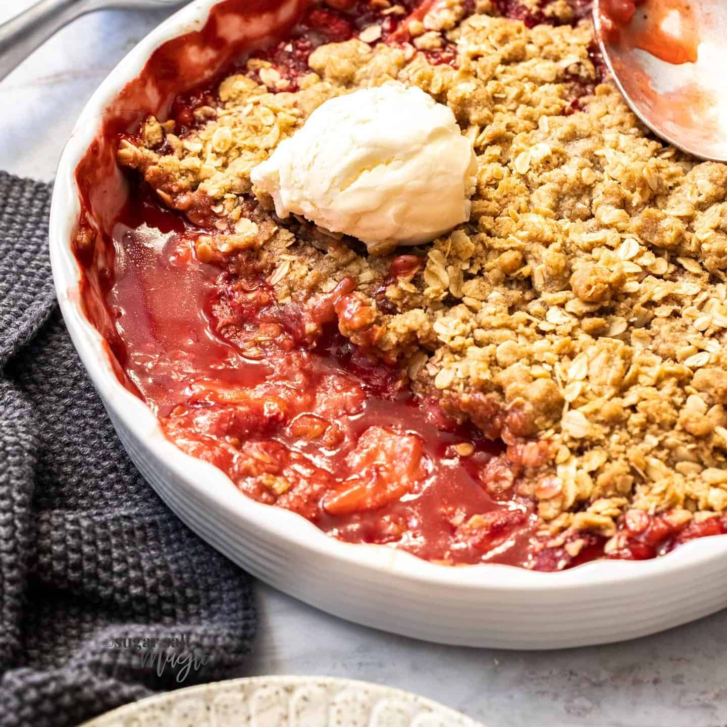 A white pie dish filled with baked strawberry crisp with a dollop of ice cream on top.