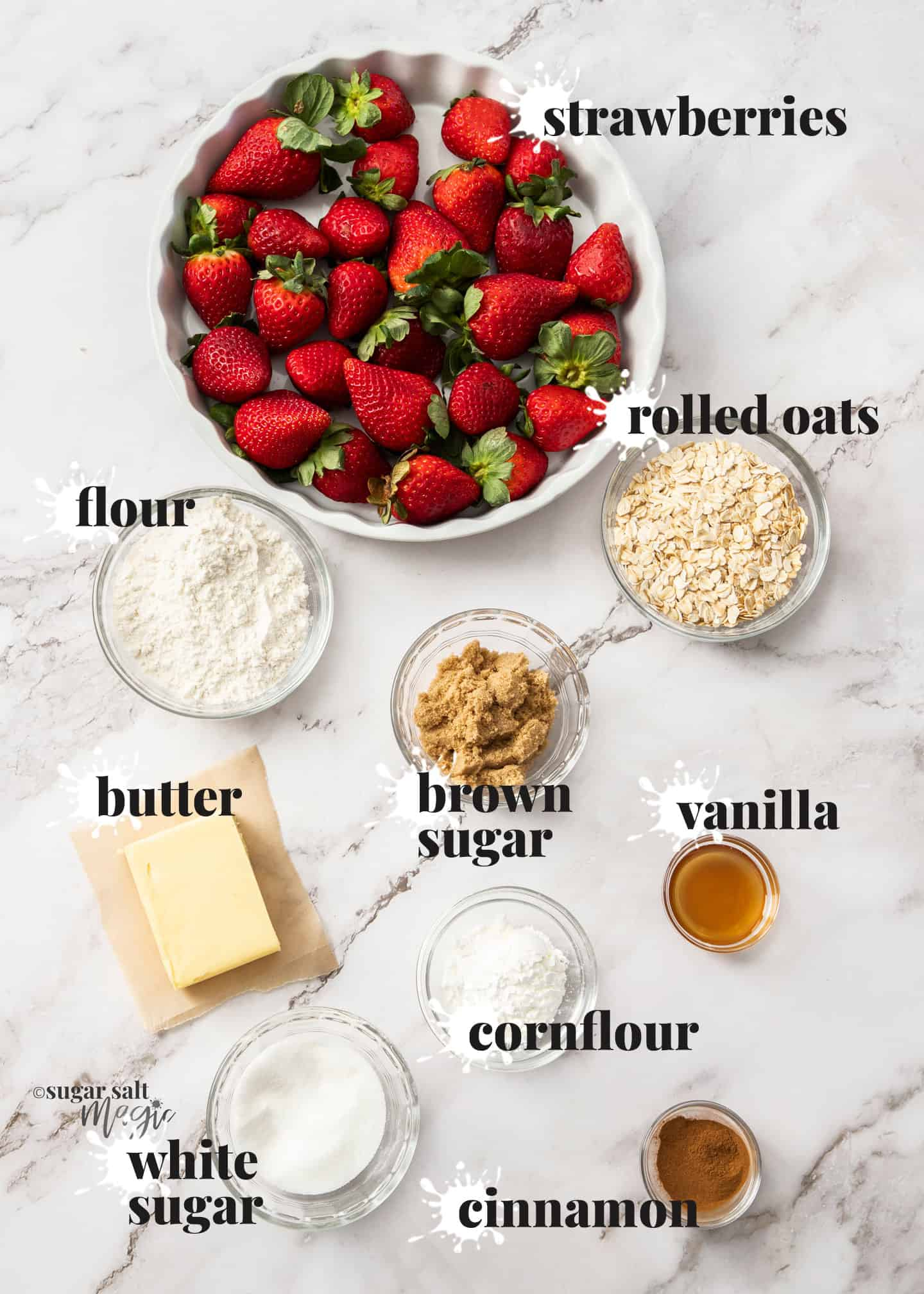 Ingredients for strawberry crisp on a white marble surface.