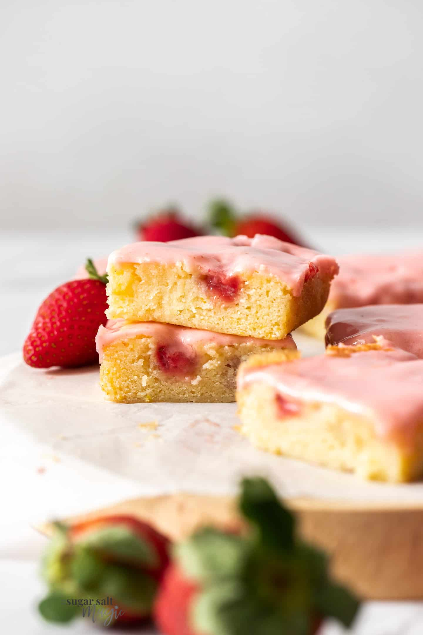 A stack of 2 strawberry blondies with more in front and a strawberry behind.