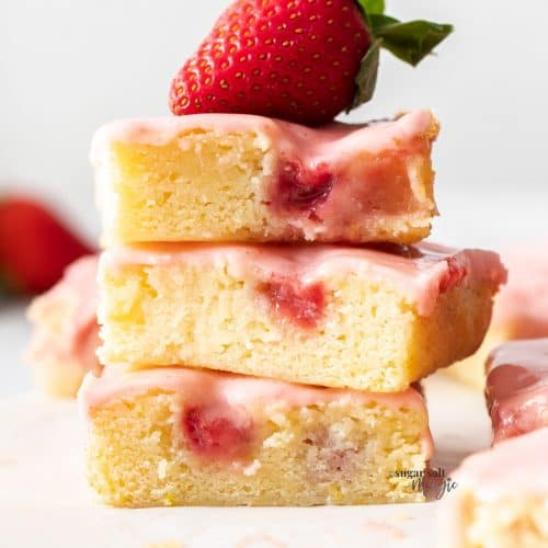 A stack of 3 strawberry blondies with a strawberry on top.