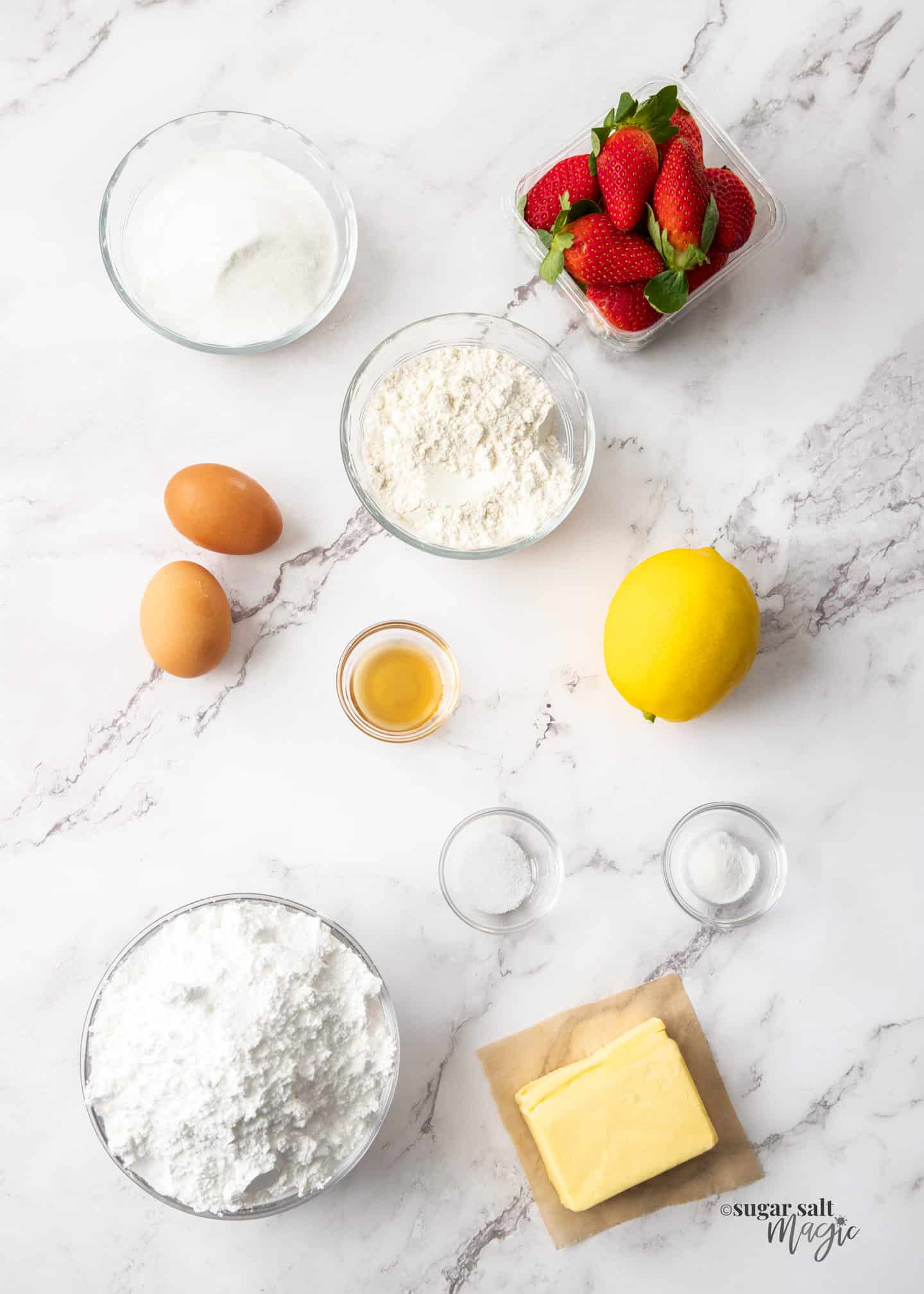 Ingredients for strawberry blondies on a white marble worktop.