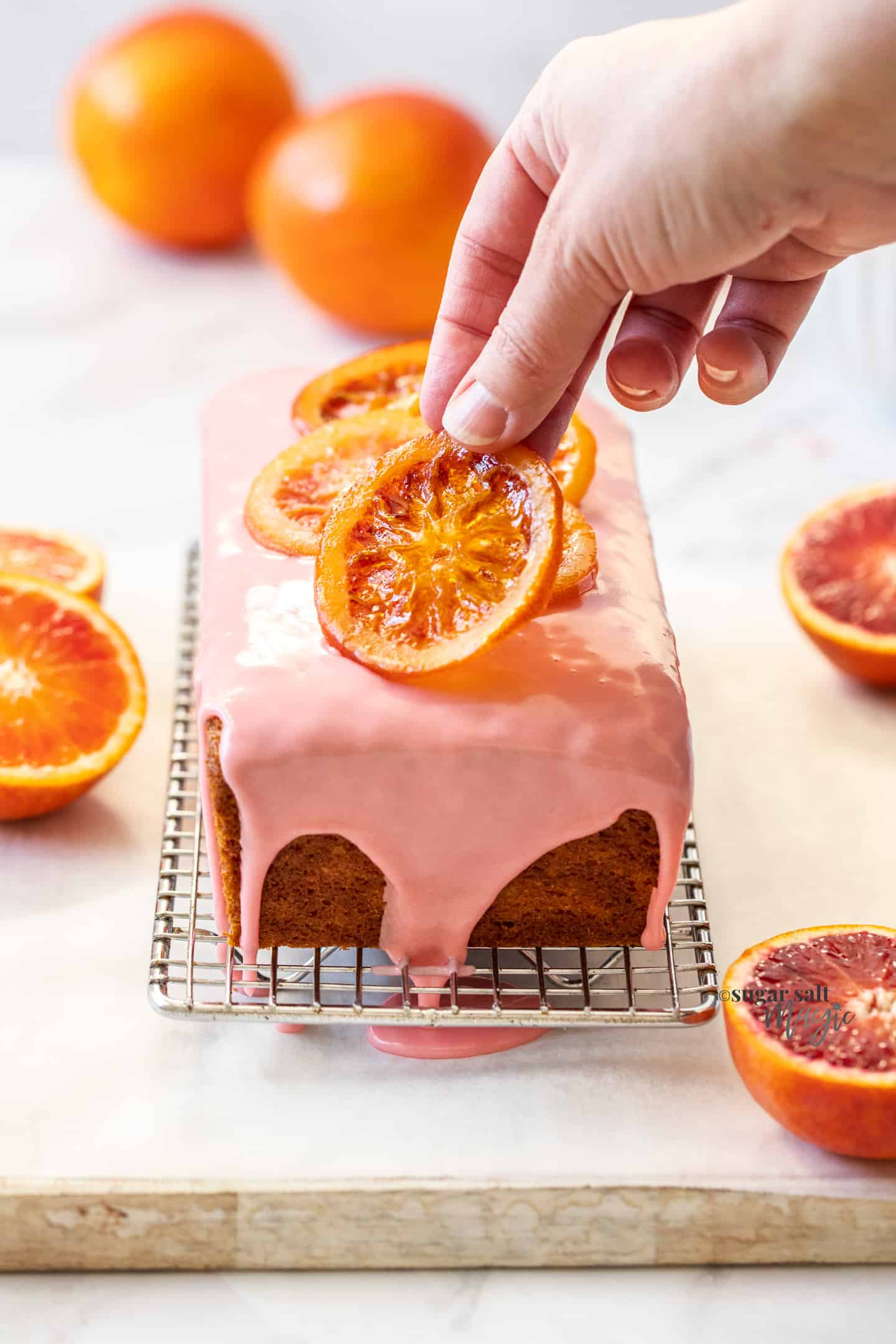 A hand placing a candied orange slice on a loaf cake