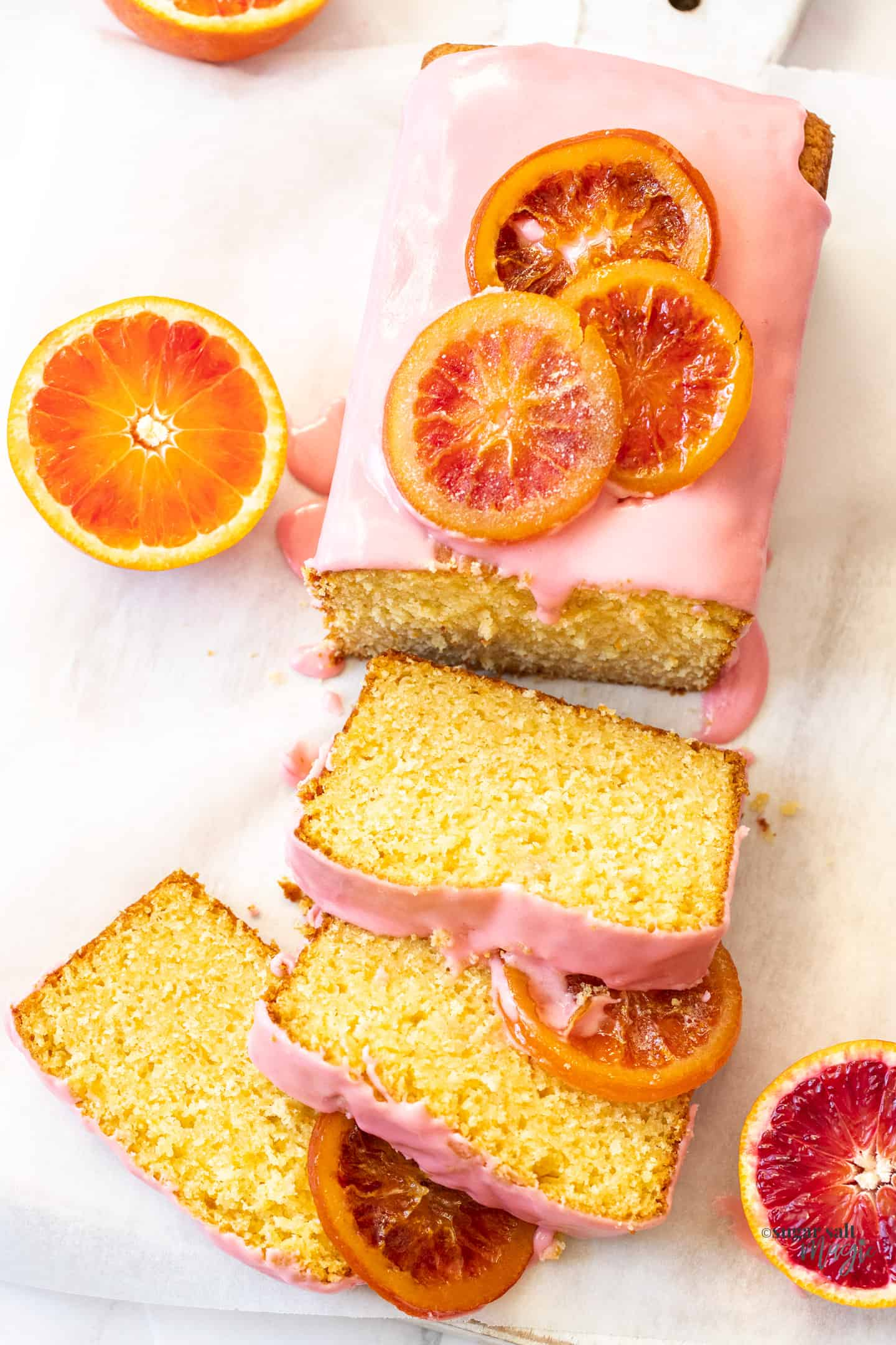 Top down view of an orange loaf cake with slices cut from it.